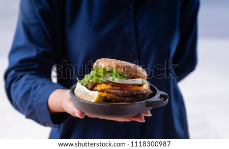Homemade hamburger served on rustic plate, waitress serving in hands  #1118300987