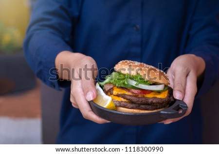 Homemade hamburger served on rustic plate, waitress serving in hands  #1118300990