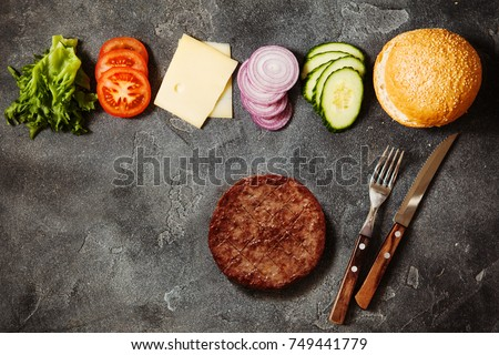 Homemade hamburger with ingredients on dark slate background top view with space for text