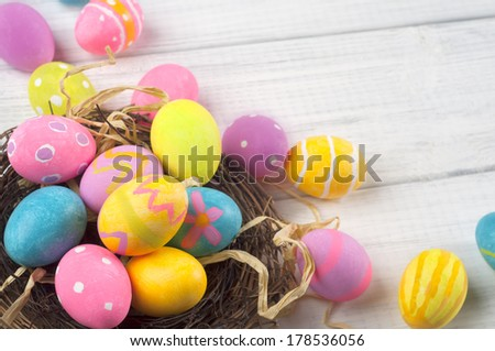Homemade Hand Painted Easter Eggs of Various Colors in a Nest on White Board Background with room or space for copy, text, words.