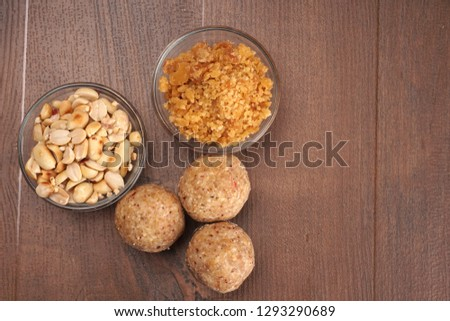 Homemade healthy and sweet groundnut or peanut and Jaggery Laddoo, delicious indian sweet served on a wooden background.Roasted peanut and Jaggery in bowl.