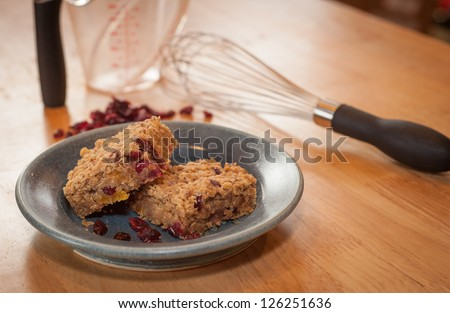 Homemade healthy breakfast oatmeal bars on a pottery plate. Bars are filled with dried fruit such as cranberries, apricots and dates for a fiber filled snack.
