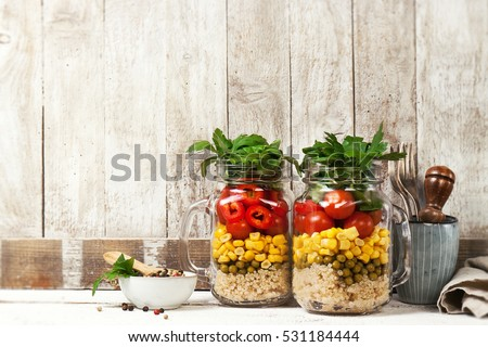 Homemade healthy layer salad in mason jars on a wooden background. Healthy life, food, detox concept