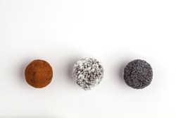 Homemade Healthy Raw Energy Balls with carob, a poppy and coconut isolated on white background, top view