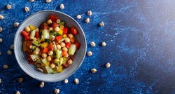 Homemade healthy vegan salad, with chickpea , tomato, cucumber, paprika served in a bowl. Healthy meal, on a dinner table.
