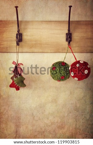 Homemade holiday ornaments hanging on antique wall hooks