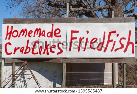 Homemade HOMEMADE CRAB CAKES FRIED FISH sign posted on plywood boards.