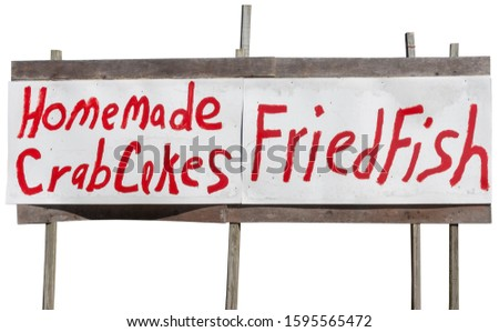 Homemade HOMEMADE CRAB CAKES FRIED FISH sign posted on plywood boards. Isolated.