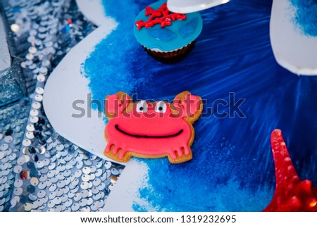Homemade homemade gingerbread cookies in the form of crab, turtile, octopus and a starfish on the wooden table. Space for text and selective focus. #1319232695