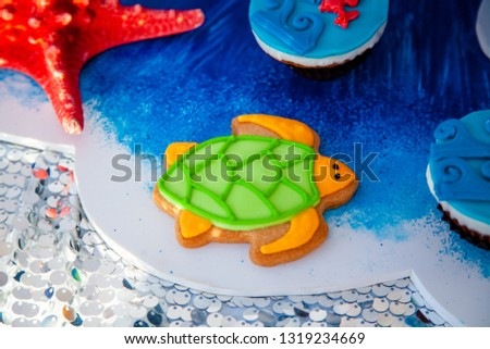 Homemade homemade gingerbread cookies in the form of crab, turtile, octopus and a starfish on the wooden table. Space for text and selective focus. #1319234669