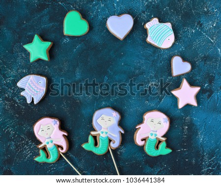 Homemade homemade gingerbread cookies in the shape of a mermaid, fish, hearts on a wooden background #1036441384