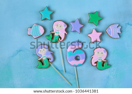 Homemade homemade gingerbread cookies in the shape of a mermaid, fish, stars on a wooden background #1036441381