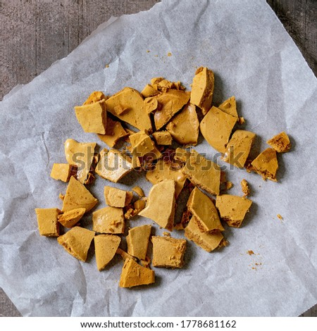 Homemade honeycomb hokey pokey or cinder toffee or dalgona korean sugar candies on baking paper over grey concrete background. Flat lay, space Stockfoto ©
