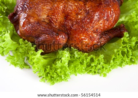 homemade hot smoked whole chicken on leaf lettuce bed isolated on white