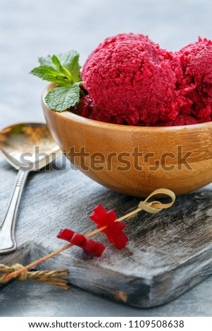 Homemade ice cream from beet in a bowl, beetroot decoration on a wooden serving board.