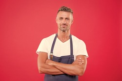 Homemade is best. Cook with bristle crossed arms on chest red background. Cook food at home. Man mature cook posing cooking apron. Fine recipe. Ideas and tips. Chief cook and professional culinary.