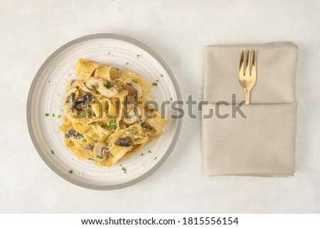 Homemade Italian fettuccine pasta with mushrooms and parmesan (Fettuccine al Funghi Porcini). Traditional Italian cuisine. Served with on white background. Top view. Foto d'archivio ©