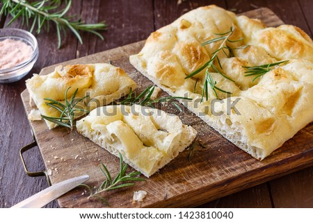 Homemade Italian Focaccia Modenese, with rosemary and olive oil on a rustic wooden background.