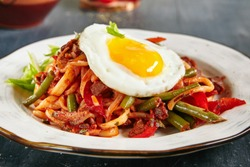 Homemade Kaurma Lagman or Laghman with Vegetables, Beef Meat and Oriental Spices Close Up. Rich Asian Dish of Fried Home-Made Noodles Prepared from a Stringy Dough, Served with Egg