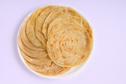Homemade kerala Porotta or paratha,layered flat bread made using maida or all purpose wheat flour arranged in a white ceramic plate with white background.
