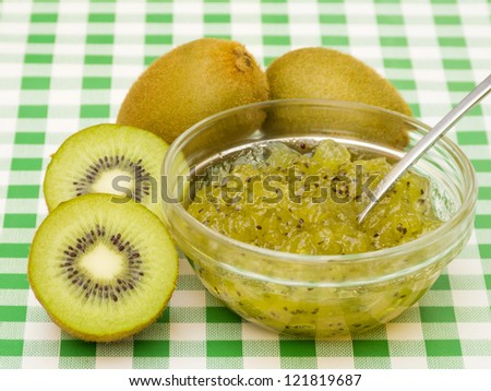 Homemade kiwi jam with fruit on green tablecloth - stock photo