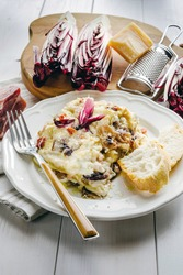 Homemade lasagna with Treviso radicchio, speck and bechamel sauce on the plate above the table