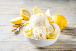 Homemade lemon vanilla ice cream with fresh lemon slices. Sweet and sour summer dessert. Wooden background copy space