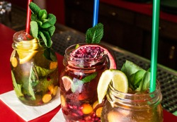 Homemade lemonade ice tea colorful icetea drink with fresh sweet fruits mint leaves in glass on the rocks with straw