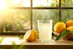Homemade lemonade on kitchen with basket full of lemons with a window and a lemon grove in the background. Front view. Horizontal composition.