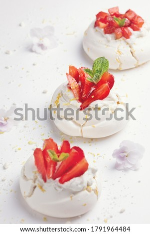 Homemade meringue dessert Pavlova cake with fresh strawberries and mint. Summer dessert. French cake. Confectionery. Classic dessert. Strawberry dessert