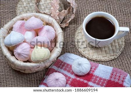 Homemade meringue kisses and coffee cup. Meringue cookies in wicker basket on natural sackcloth background Сток-фото ©
