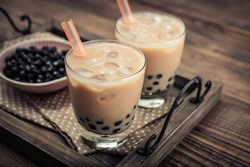 Homemade Milk Bubble Tea with Tapioca Pearls on wooden background