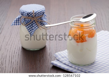 Homemade milk yogurt with peach or apricot jam in glass pot and metal spoon served on linen napkin, wooden table