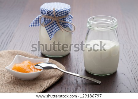 Homemade milk yogurt with peach or apricot jam in porcelain bowl and metal spoon served on linen napkin, wooden table