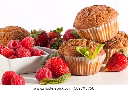Homemade muffins with fresh strawberries and raspberries on white table