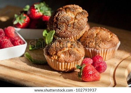 Homemade muffins with fresh strawberries and raspberries on wooden desk. See series.
