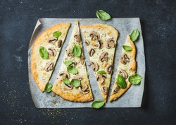 Homemade mushroom pizza with basil cut in slices on baking paper over black stone background, top view, horizontal composition