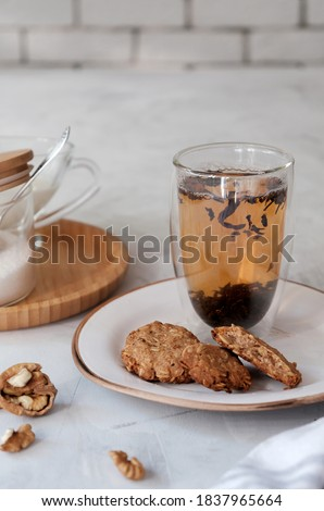 Homemade oatmeal cookies and a hot tea in the double bottom glass . Breakfast concept in neutral tones. Vertical composition
