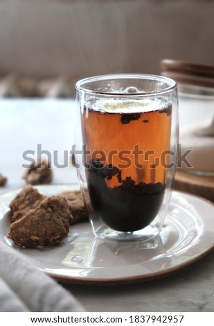 Homemade oatmeal cookies and a hot tea in the double bottom glass . Breakfast concept. Vertical composition