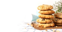 Homemade oatmeal cookies with peanuts and raisins on the kitchen table, white background, free space for text. Stack of oatmeal cookies close-up, copy space.