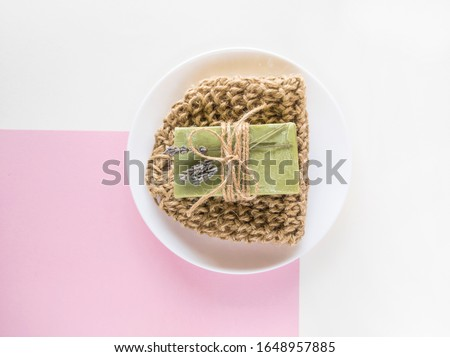 Homemade olive soap bar and textile washcloth on minimalistic background. Set of plastic free and zero waste body care items.