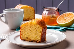 Homemade orange cake. Table with a piece of cake and cup of coffee.