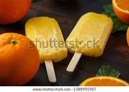Homemade orange popsicles, ice lolly, on wooden table. Summer food.