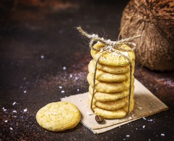 Homemade organic coconut cookies with a whole coconut on a brown background. Sweet pastries with coconut flour are gluten-free, low in carb. Keto diet. Sweet present. Healthy and tasty dessert