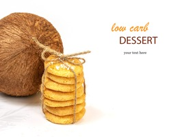 Homemade organic coconut cookies with a whole coconut on a white background with easy removable sample text. Sweet pastries with coconut flour are gluten-free, low in carb. Keto diet. Healthy dessert