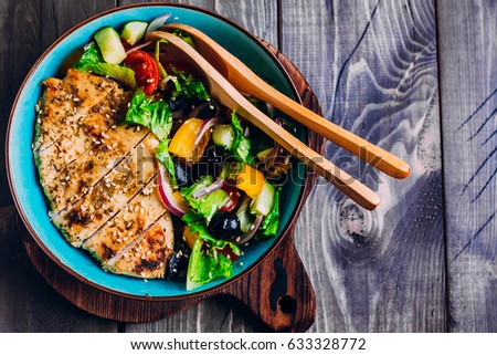 Homemade Organic Greek salad and roasted chicken in plate on wooden table background. Top view with copy space. Healthy food