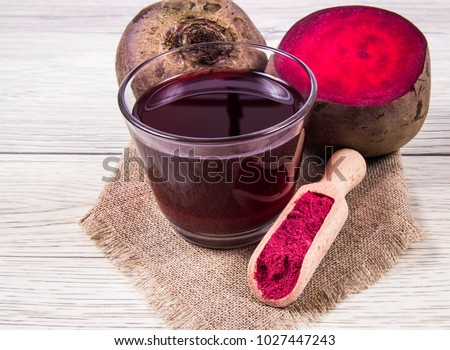 Homemade organic healthy beetroot juice and fresh vegetables on rustic wooden background.