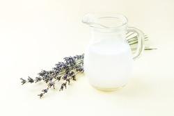 Homemade organic yogurt or sour milk in glass jug next to dried lavender flowers