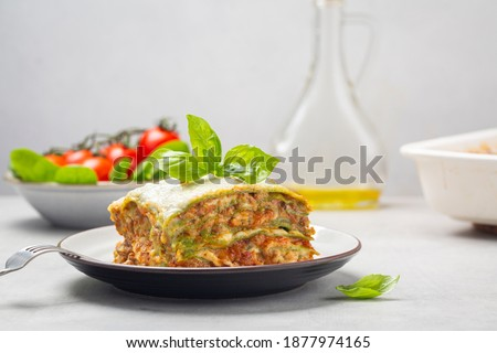 Homemade oven-baked green lasagna - Lasagne alla bolognese with spinach in the dough, ragu - meat sauce, bechamel and parmesan cheese. Italian food.  Horizontal image.