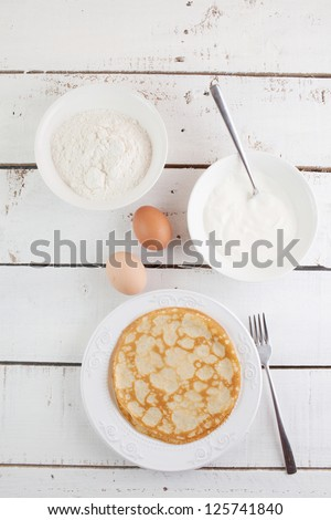 homemade pancakes and ingredients on wood table